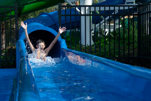 Boy exiting fast slide with a splash